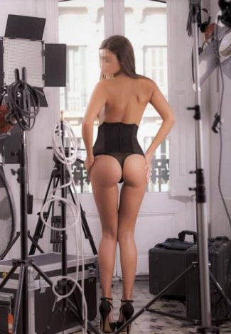 Istanbul escort agency lover Olia is standing on high heels in a photo studio being dressed only in something that covers a half of her body