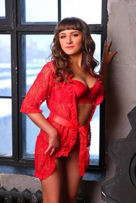 Ankara escort katalog has Lika standing in red attire near the window