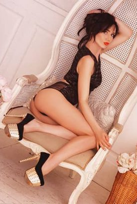 Adana VIP escort bayan Sonia in black is sitting in the big chair, bigger than she is