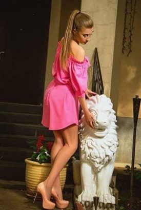Istanbul eskortlar Kristina in the nice pink summer dress cuddling a stone sculpture of a lion